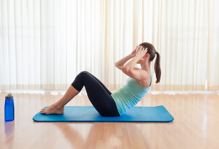 Woman doing sit ups at home.