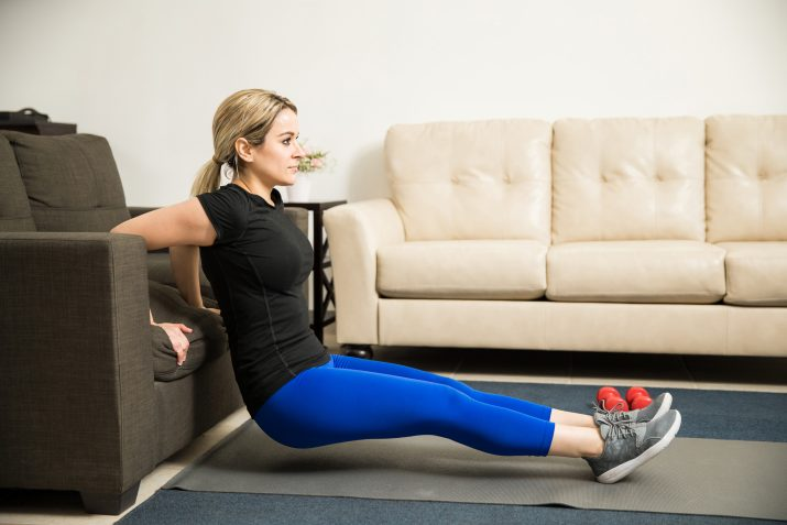 Profile view of a pretty young woman doing tricep dips leaning on a couch in her living room